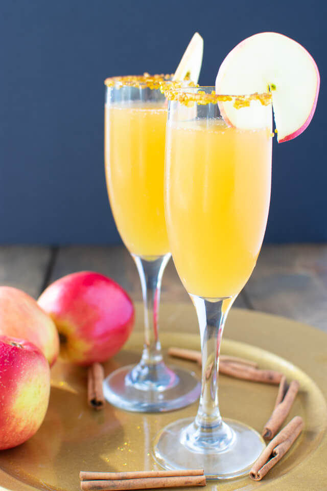 Two apple cider mimosas on a plate with apples and cinnamon sticks
